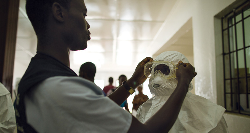 putting on protective gear against Ebola