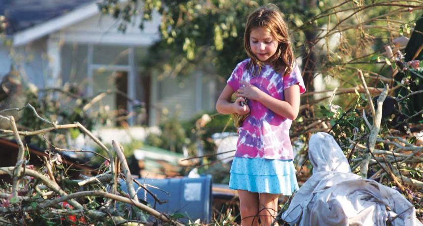 girl standing in wreckage of Hurricane Katrina