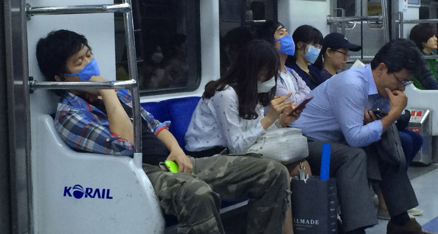 people wearing surgical masks on subway in Seoul, South Korea