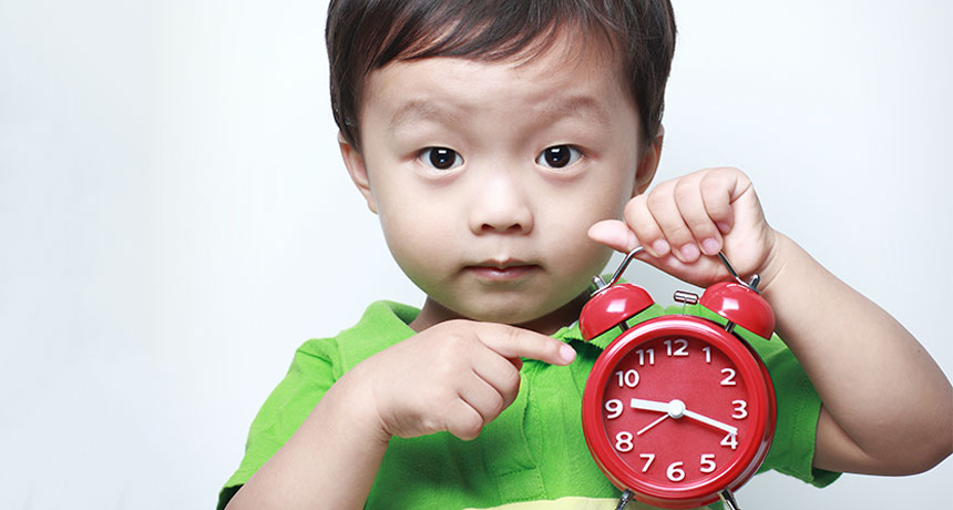 toddler holding alarm clock