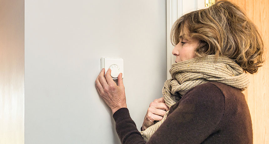 woman bundled up in scarf adjusting thermostat