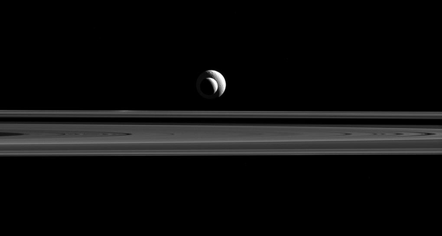 Cassini image of Enceladus over Saturn's rings