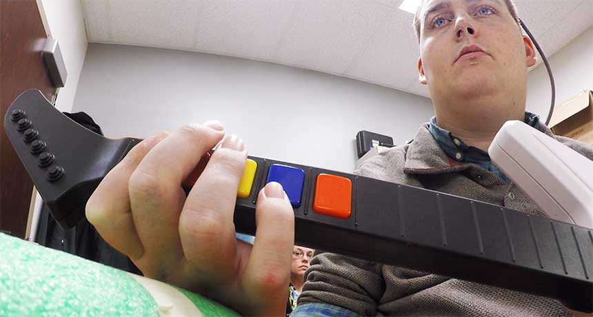 a paralyzed man playing a guitar video game