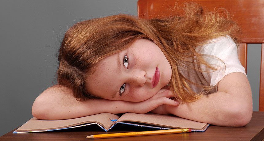 girl with her head down on book