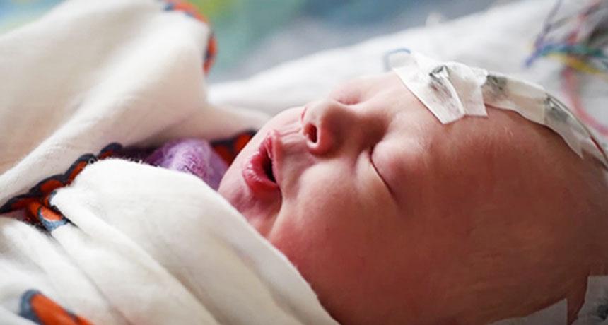 newborn baby wearing electrodes