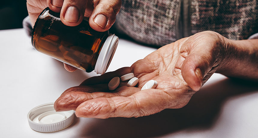 elderly person taking pills