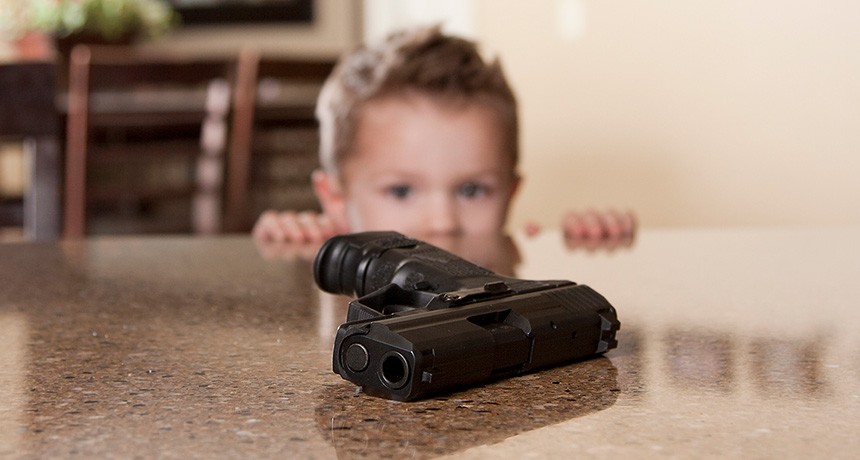 child looking at firearm