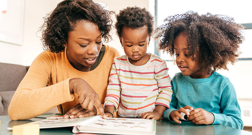 parent reading to two kids