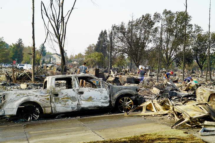 a photo of the damage from the Tubbs Fire including a burned out white pickup truck and debris from demolished homes
