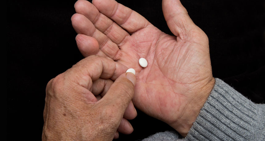 person holding aspirin tablets