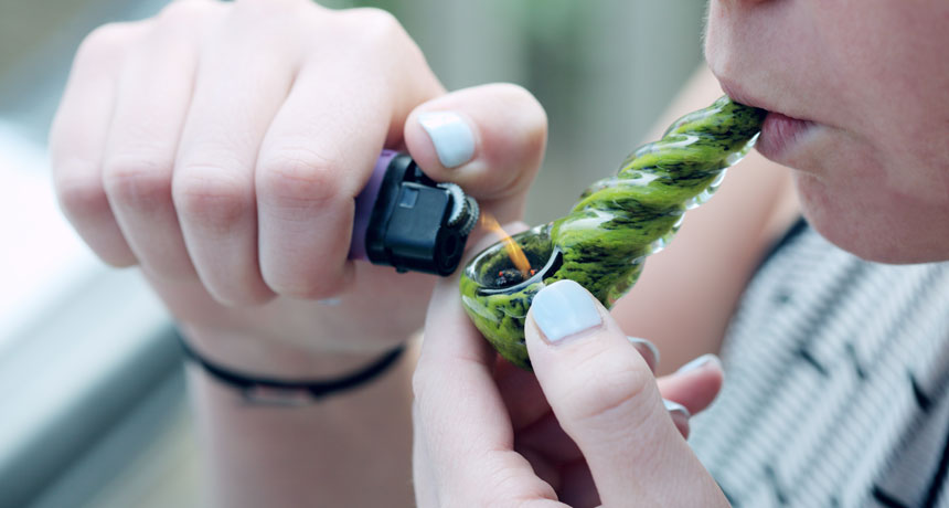 person lighting marijuana pipe