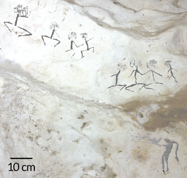 a photo of human figures painted on a cave wall in Borneo