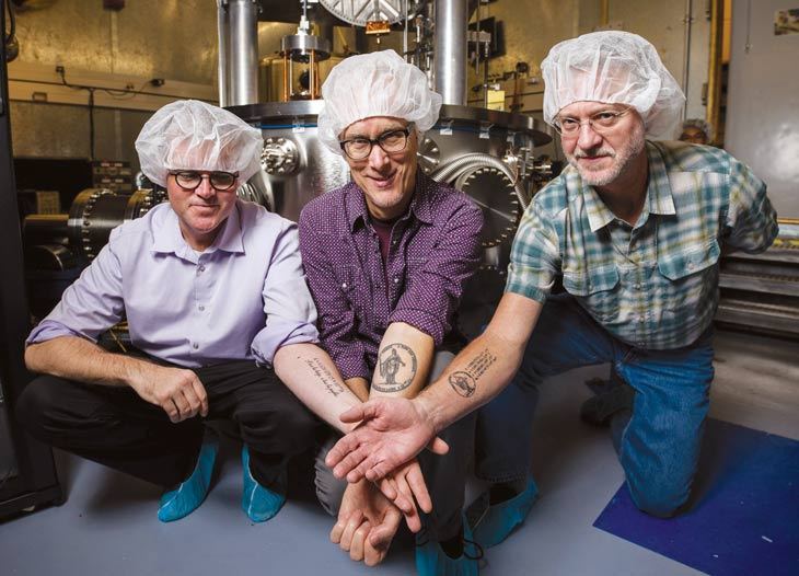 three scientists showing their forearm tattoos, of the Planck constant