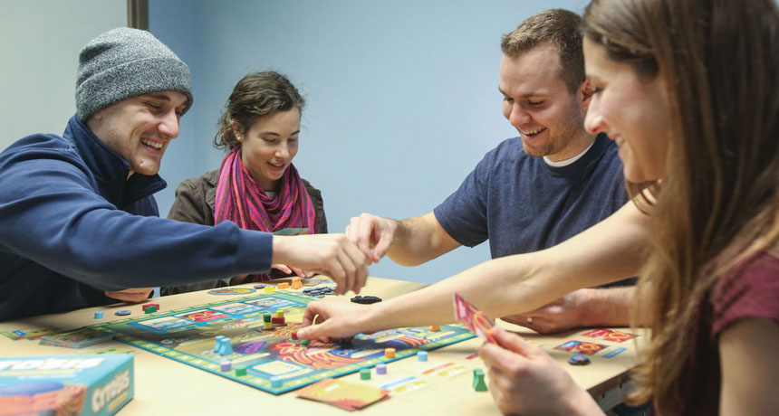 people playing a science board game