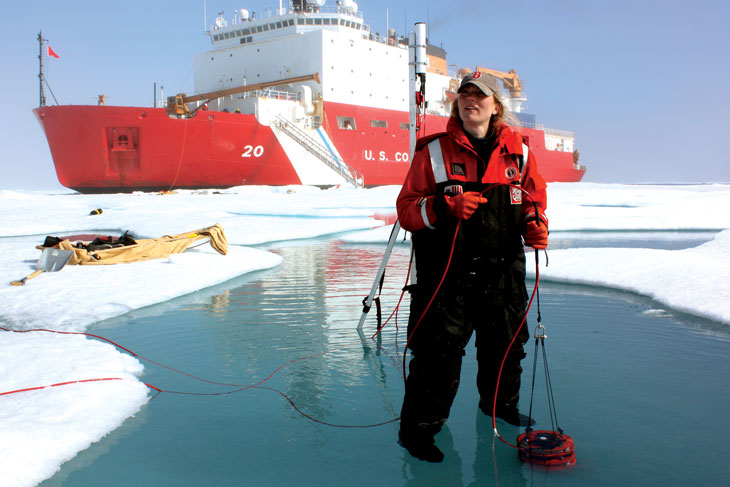 polar scientist Karen Frey stands in a melt pond