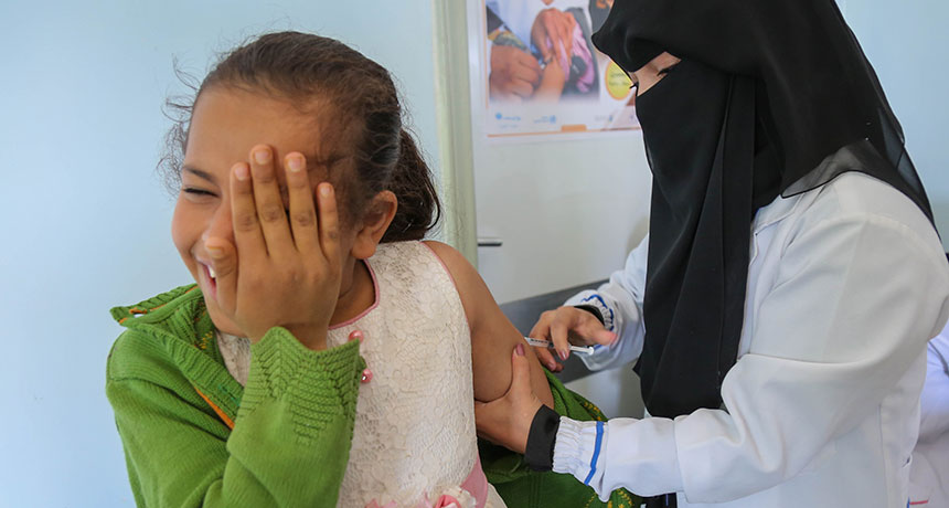 girl in Yemen getting measles shot