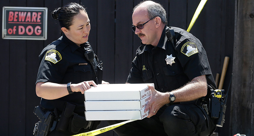 police officers with evidence boxes
