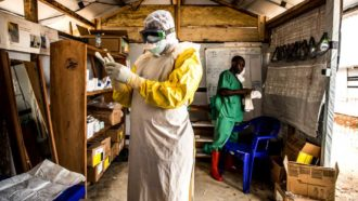 a photo of a doctor putting on protective gear