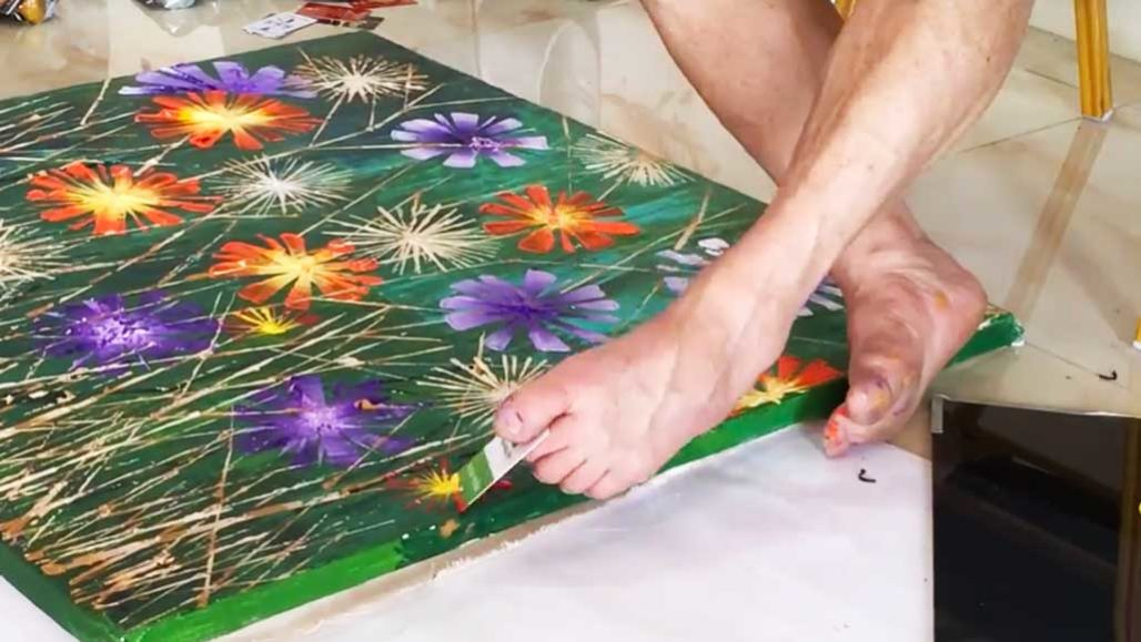 person painting with paintbrush held in their toes