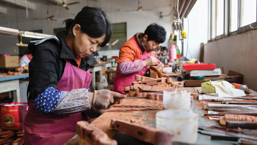 Artisans carving rosewood