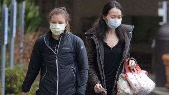 two women wearing masks