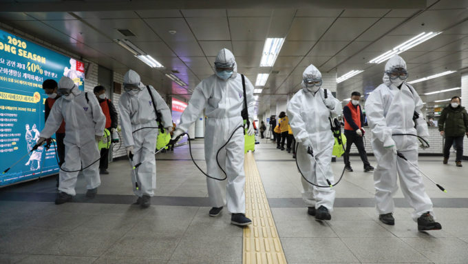 people in clean suits spraying a subway tunnel
