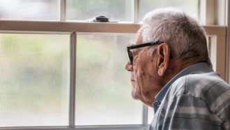 elderly man looking out window