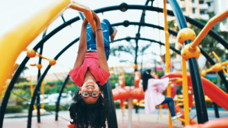 Kid hanging upside down on a jungle gym