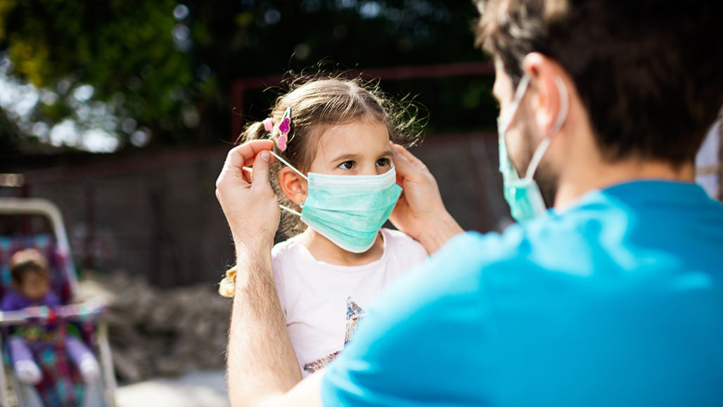 Parent putting mask on child