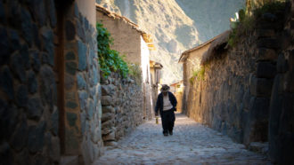 Peruvian man walking up cobblestone path
