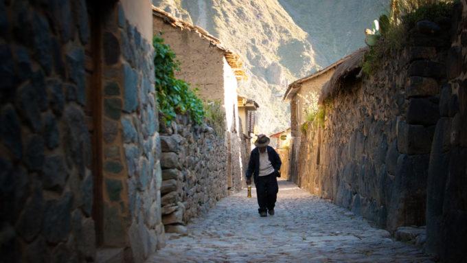 Peruvian man walking up cobblestone path