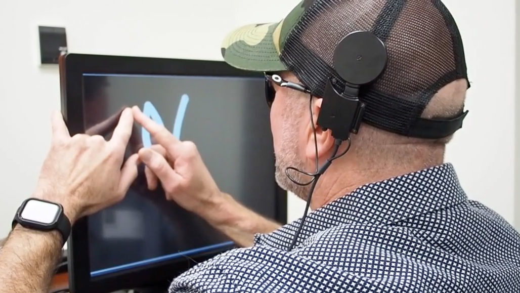 man standing at a screen drawing a letter with his fingers