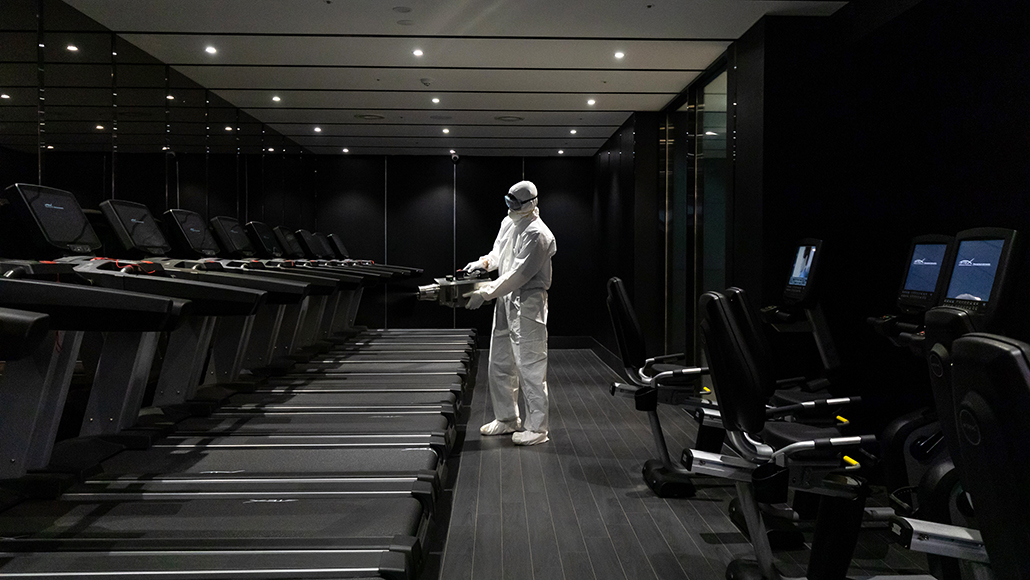 Worker spraying disinfectant in a fitness center