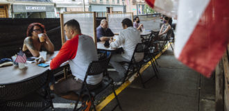 people sitting at distanced tables in a restaurant