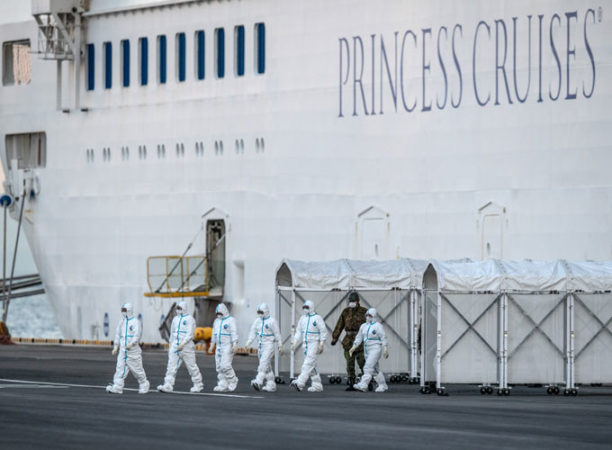 photo of people leaving cruise ship in hazmat suits