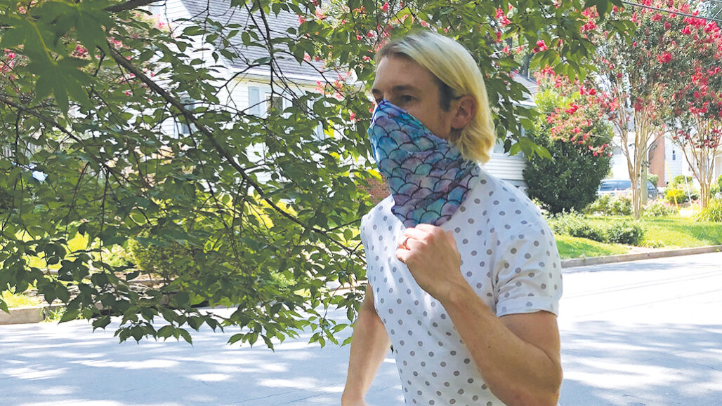 man running while wearing a neck gaiter over his nose and mouth
