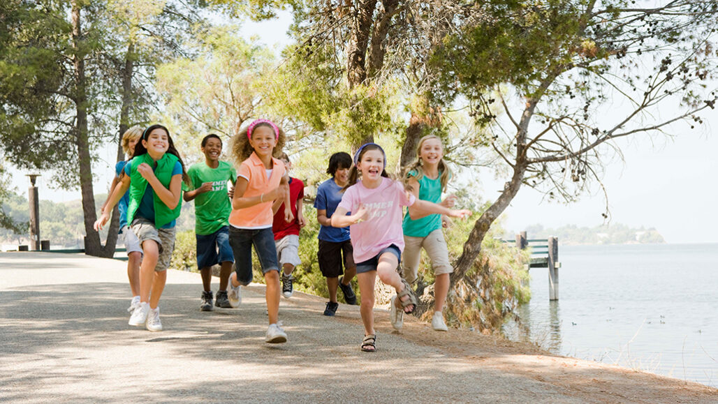 group of children at camp running along a path
