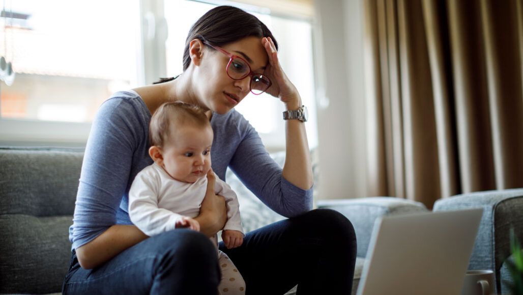 mother holding young child and looking in frustration at laptop