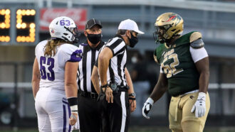 college football players talking to masked referees