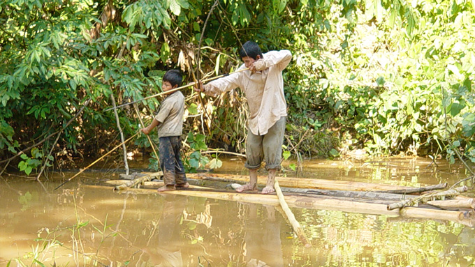 members of indigenous tsimane in Bolivia fishing with bow and arrow