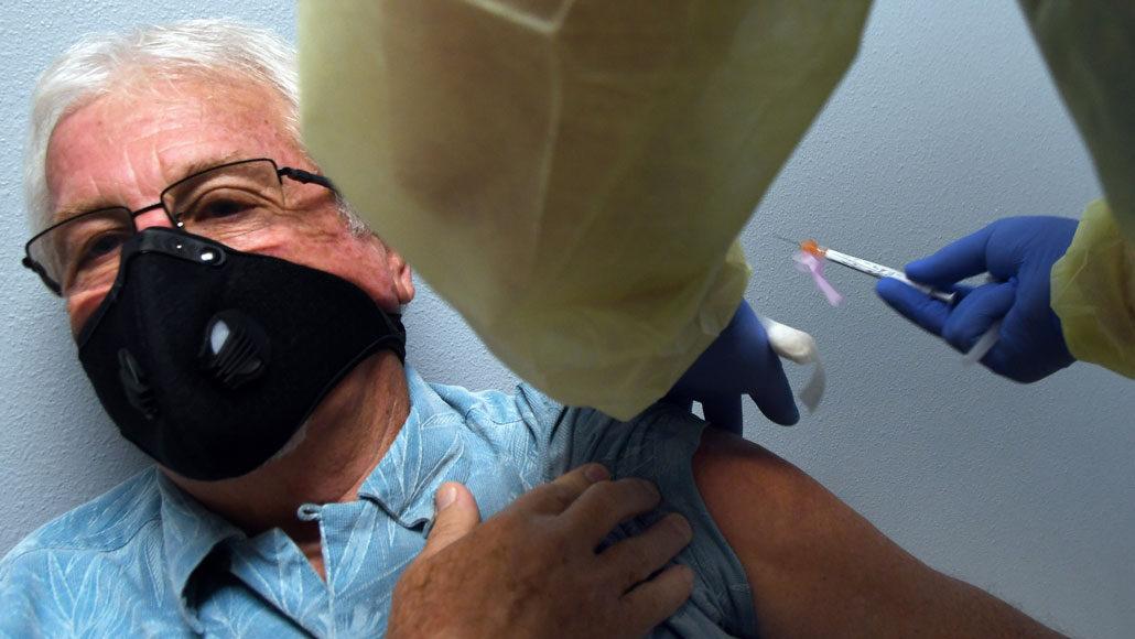 older man wearing a mask receiving a shot