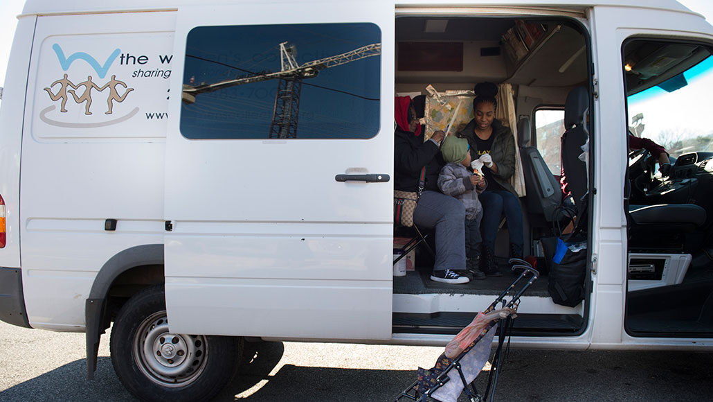 photo of a parked van with side door open; young woman and toddler sitting inside
