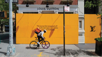 bike messenger in front of a boarded up Louis Vuitton store