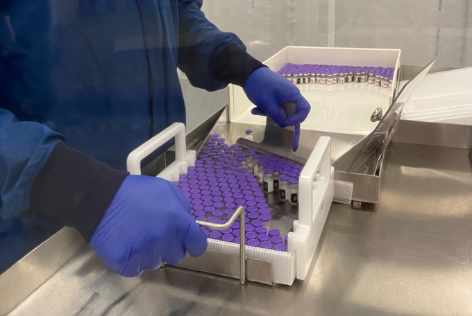worker loading vials of COVID-19 vaccine into containers