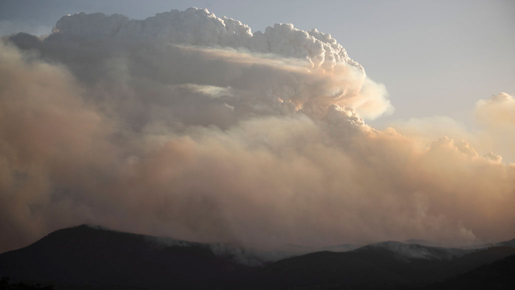 big cloud of smoke hovering over the top of the hill tops