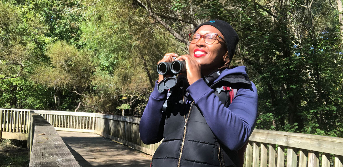 Deja Perkins standing in a park and holding a pair of binoculars