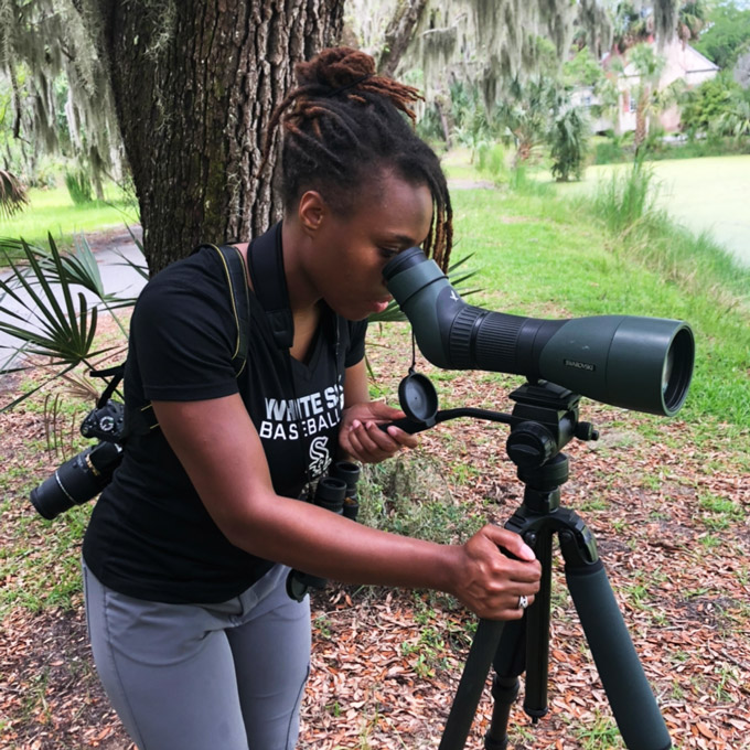 Deja Perkins birding and looking through a telescope on a tripode