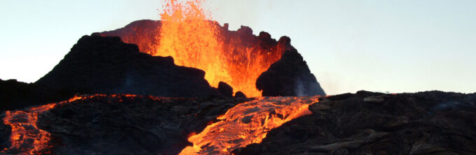 top of volcano, with river of orange lava flowing down it