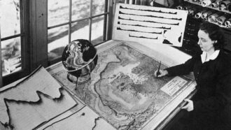 Marie Tharp looks over a map on a table