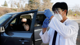 woman getting vaccinated at a drive-through clinic